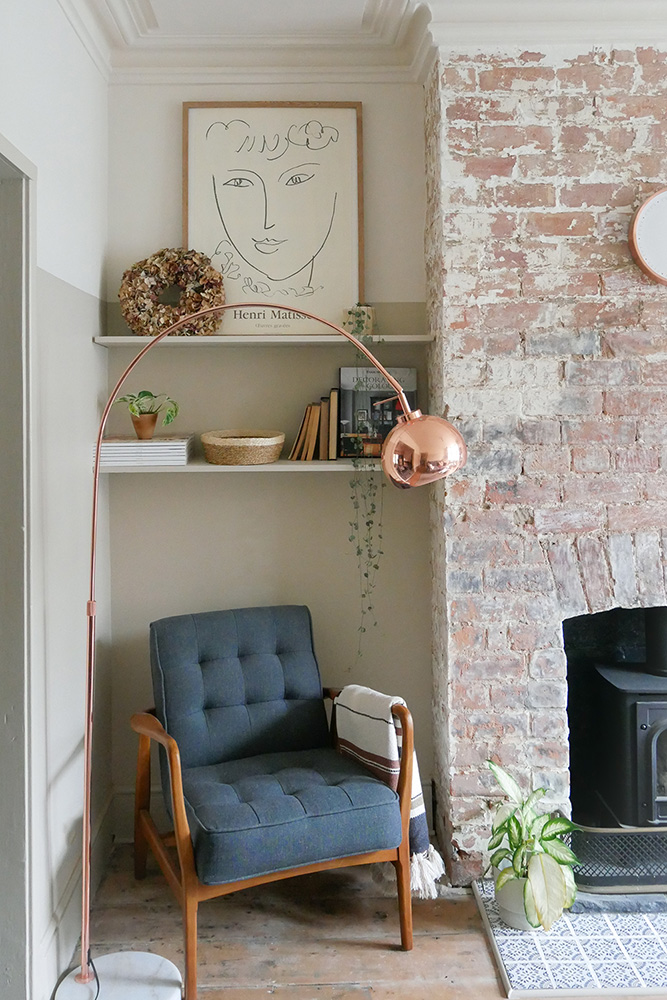 Close up of the alcove next to a brick chimney breast with rose-y ping brick and a cream paint patina