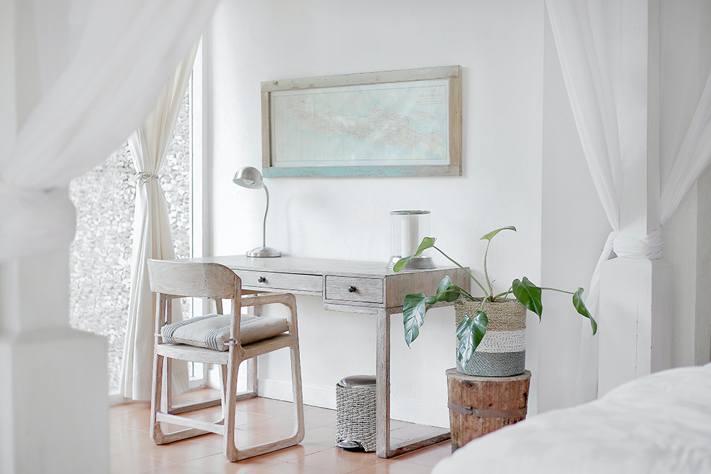 A chic minimalise desk scene with a plant in a rattan basket