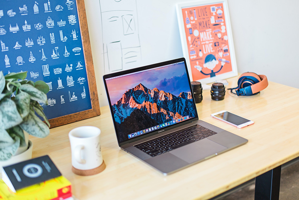 An open Macbook Pro on a desk surrounded by peach-and-blue-coloured accessories and framed prints