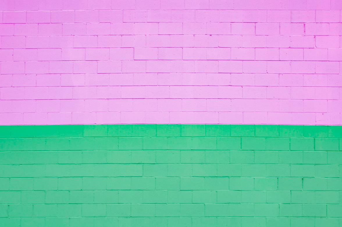 a brick wall painted half in green and half in bubble gum pink
