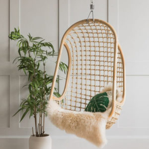 egg-shaped rattan chair with sheepskin and cushions