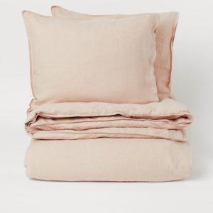Set of powder beige bed linen folded up in a pile